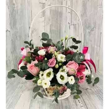 Σύνθεση με λουλούδια σε καλάθι σε λευκές και ρόζ αποχρώσεις.
